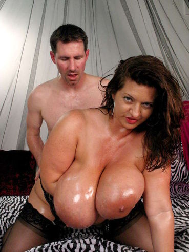 Plumper Maria Moore with gigantic oiled tits takes off her red corset and gets nailed by skinny man