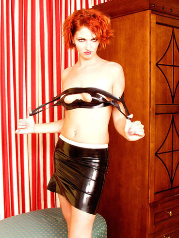 Flirty redhead Ivy Red in black and white latex skirt shows her snatch and tits