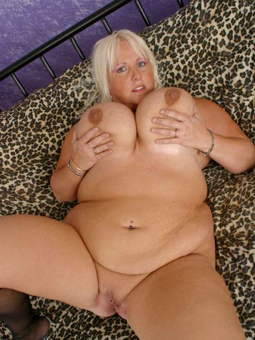 Smiling blonde plumper Daphne Stone with giant tits and shaved pussy removes her black lingerie