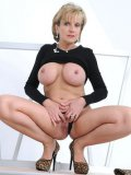 Mature woman Lady Sonia in black shows off her shapely huge tits and shaved snatch