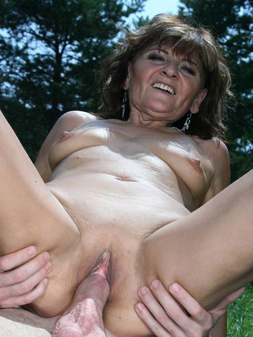 Skinny boy fucks shaved pussy of slim mature lady Ilona in the outdoors