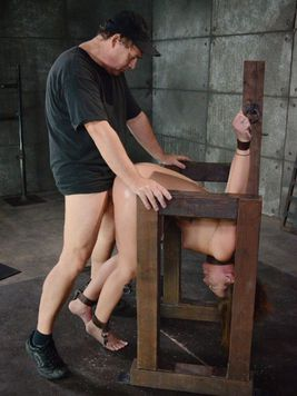 Red haired Maddy OReilly flipped upside down while her bondage master makes her moan with toys.