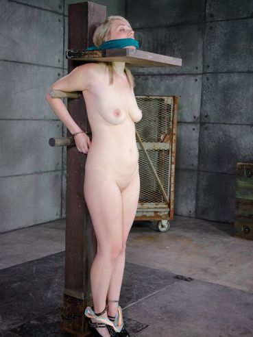 Cute and blonde Winnie Rider spider gagged and in stocks while having her body bondage teased.