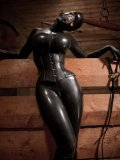 Latex lady Bianca Beauchamp in black tries on amazing horse mask in the barn