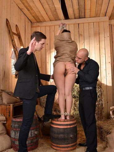 Tigerr Benson put into a potato sack during bondage and has to please two massive, shaved cocks.