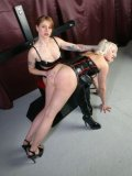 Blonde Betty in black dress and heels gets her bare ass spanked by brunette Domina Hera.