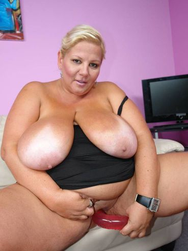 Blonde haired BBW mom Wonder Tracy with massive tanlined tits drills her hole with red dildo
