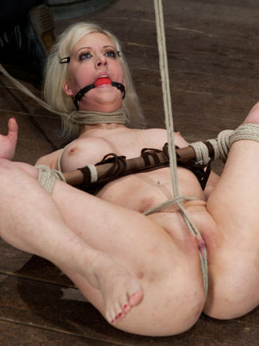 Gagged bitch Cherry Torn is tied up and gagged and her shaved pussy lips pulled with ropes.