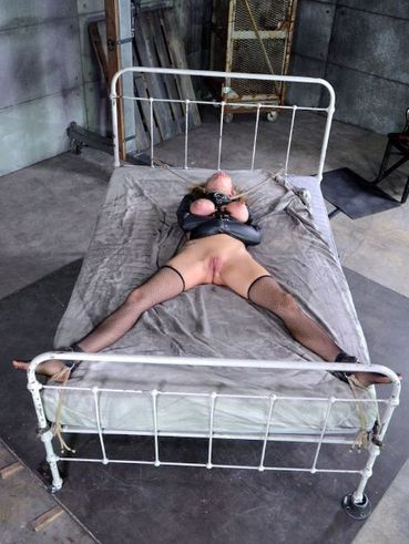 Rain DeGrey on her knees getting her tits pinched and pulled on head while in kinky bondage.