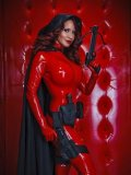 Latex clad beauty Bianca Beauchamp poses with crossbow in red rubber room