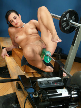 Ava Ramon takes green rubber robot-cock in her shaved eager pussy in the fitness room