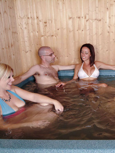 Shaved headed dude gets his dick jerked by Kelly Hart and her friends in jacuzzi