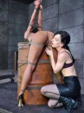Nikki Darling tied up to a barrel and getting BDMS stimulated bu kinky and slim Elise Graves.