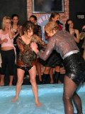 Clothed Leony April does her best to win in oil wrestling match at the all-girl party