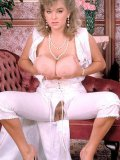 Playful chubby lady Rhonda Baxter dressed in white exposes her giant tits and bush