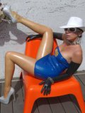 While Stella Van Gent is wearing blue latex she poses out in the sun while her tits pop out.