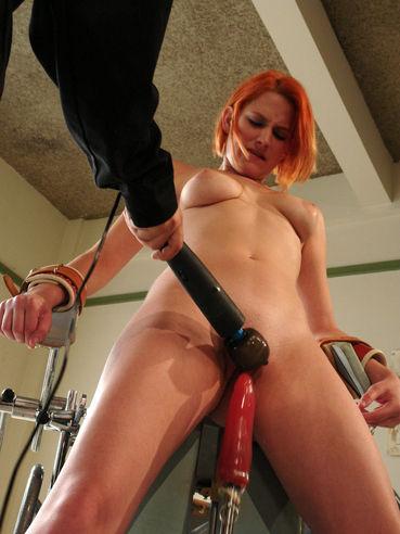 Standing redhead Addie Juniper with soft cuffs on her hands gets drilled by fucking machine