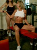 Bodybuilder Tia works out and gets her big tits fondled by supporting Deb