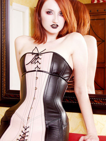 Pierced gothic model Kendra James takes off her leather corset and poses naked on red couch
