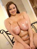 Chubby brown haired girl Terri Jane strips naked and plays with her massive oiled tits
