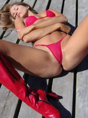 Playful hair arm lady Lori Anderson in sexy red mini bikini wets her body by the lake