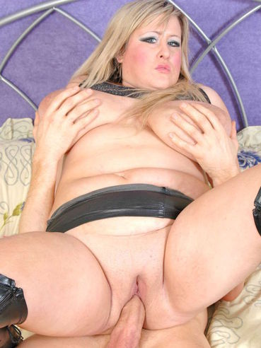 Bulky blonde slut Leah Jayne in black leather skirt and boots gets hardored on the bed