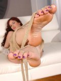 Mira Varga flashing her shaved muff and making foot fetish lovers go crazy while posing with feet.
