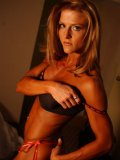 Slim sexy muscle lady Jaime Franklin in black lingerie poses in the semi-dark of the bedroom