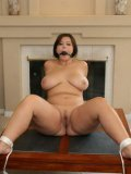 Naked naturally busty chubby brunette London Andrews is tied to table in the living room