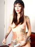 Busty Emma J with countless tattoos all over her body removes her white undies