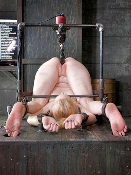 Bleached blonde Delirious Hunter is upside down while filled and stretched with bondage toys.