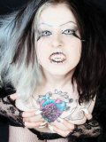 Gothic Mad Sophie dressed in black exposes her tattooed chest and shaved snatch