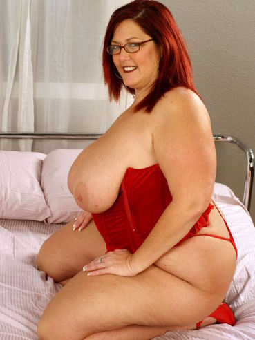 Four-eyed mature redhead fattie Peaches Larue in red lingerie has sex with black dude