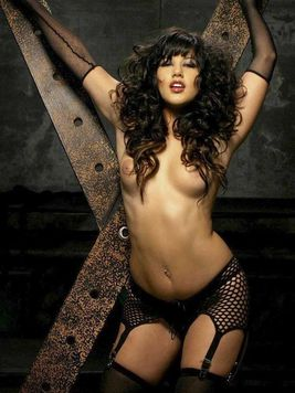 Long haired sexy brunette Sunny Leone shows off her body in the dark of the dungeon
