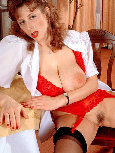 Busty BBW redhead Ivana in white blouse, red underwear and black stockings bares her assets
