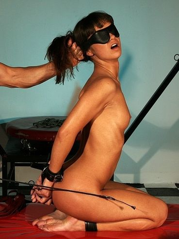 Angelina Crow with cuffs on her ankles and with clamps on her pussy lips gets her ass fucked