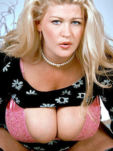 Chubby big titted blonde Gaynor in black stockings demomstrates her pink lace bra and panties