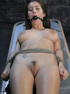Gagged big titted April Oneil tied to bondage table gets her pussy vibrated