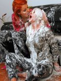Blonde Kathy Anderson and her redhead friend cover each others clothes and hair in cream