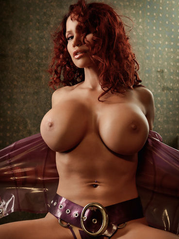 Curly haired busty redhead temptress Bianca Beauchamp peels off her rubber bra