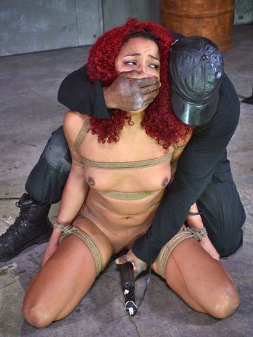 Daisy Ducati gagged and looking at the camera while her red locks fall to her face after bondage.