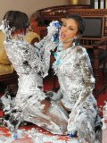 Kitty Saliery and another clothed woman cover each other in shaving foam