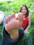 Asian girl Jenna E in blue jeans and red top shows off her neat feet in the grass
