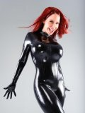 Leggy high heeled fetish model Bianca Beauchamp with long red hair poses in black latex outfit