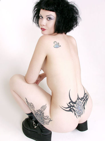 Petite tattooed goth brunette Verotika takes off her skirt, corset and thong panties