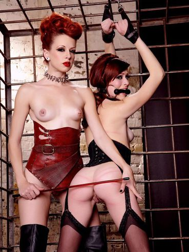 Redhead Hollis Ireland gets spanked by long legged domina and licks her boots
