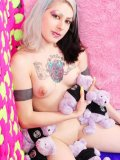 Gothic teen Mad Sophie with heavy make-up shows off her puffy pierced tits playing with plush toys