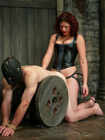 Curly haired redhead domme Venus May dressed in latex punishes masked slave Jack