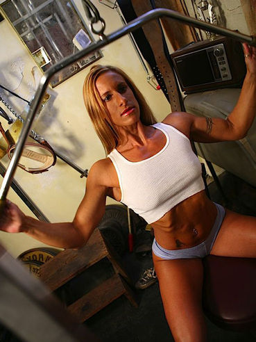Uniformed bodybuilder Vanessa Adams in tight fit shorts and top works out in the gym room