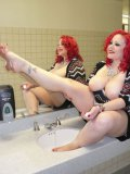 Tattooed redhead April Flores washes her bare feet in the public bathroom